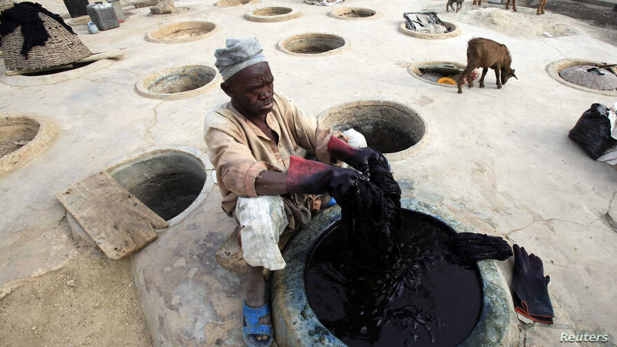 FILE - A man dyes fabrics  in traditional styles in Kano, Nigeria, Nov. 28, 2009.