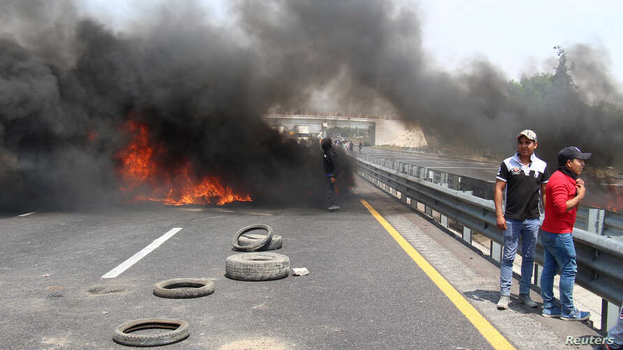 Residents burn tires to block a highway during a protest against the army after an incident with suspected oil thieves in the community of El Palmarito, on the outskirts of Puebla, Mexico, May 4, 2017.