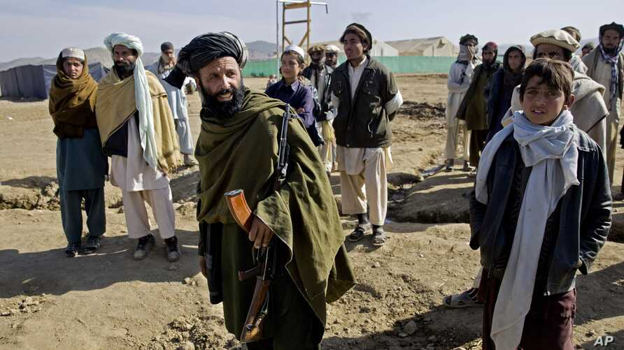 FILE - In this Monday, Jan. 19, 2015 photo, an Afghan plain cloth security personnel, holds his weapon as he walks among Pakistani refugees, at Gulan camp, some 20 kilometers (12 miles) from the border in the restive Khost province, Afghanistan.