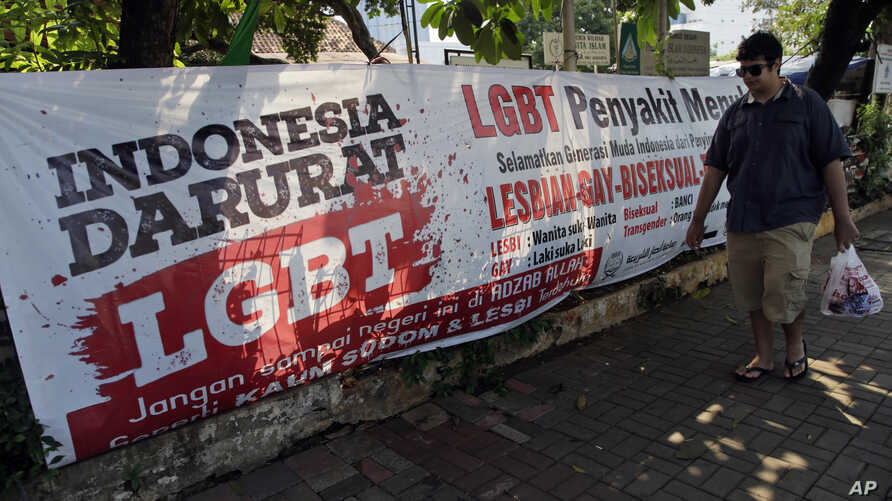 """FILE - A man walks past an anti-LGBT banner with writings that read """"Indonesia is on LGBT emergency"""" and """"LGBT is a contagious disease, save the young generation from LGBT people,"""" outside the headquarters of a conservative Islamic group in Jakarta, ..."""