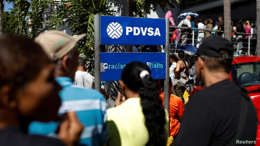 FILE - People stand next to the corporate logo of the state oil company PDVSA at a gas station in Caracas, Venezuela Jan. 6, 2018.
