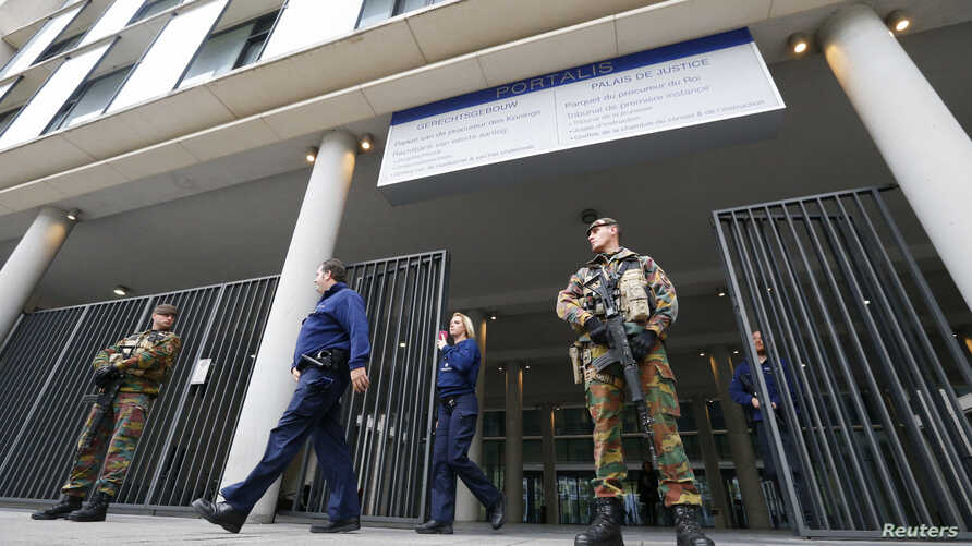 Armed soldiers stand guard outside the courthouse where suspects are expected to be questioned in the fatal shootings in Paris on Friday, in Brussels, Belgium, November 16, 2015.
