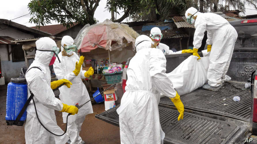 Health workers carry load the  body of a woman that they suspect died from the Ebola virus, onto a truck in front of a makeshift shop in an area known as Clara Town in Monrovia, Liberia, Wednesday, Sept. 10, 2014. A surge in Ebola infections in Liber