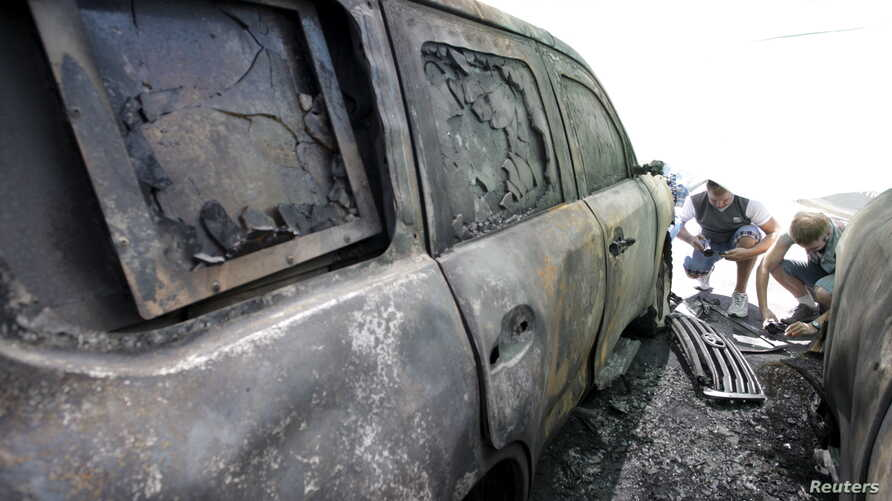 Men take photos of a car belonging to the Organization for Security and Cooperation in Europe (OSCE), which was burnt overnight, near its office in Donetsk, Ukraine, Aug. 9, 2015.