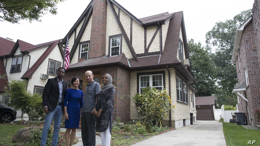 Trump In this Sept. 16, 2017, photo, Abdi Iftin, left, of Somalia, Uyen Nguyen, second from left, of Vietnam, Eiman Ali, right, of Somalia born in Yemen, and Ghassan al-Chahada, of Syria pose outside President Donald Trump's boyhood home in the Queen