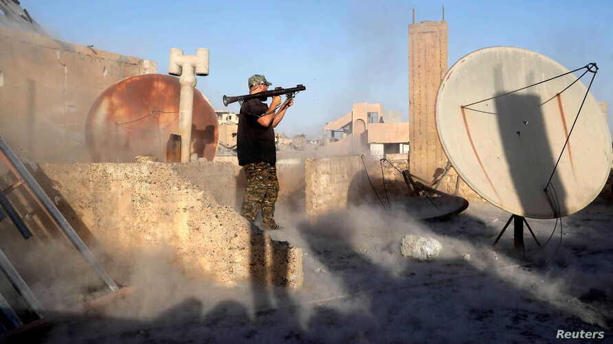 An American volunteer fighter of Syrian Democratic Forces fires an RPG during a battle with Islamic State militants in Raqqa, Syria, Oct. 6, 2017. An American surrendered to US-backed fighters in Syria in mid-September and is being held as an unlawfu...