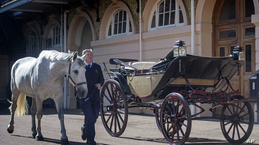 Philip Barnard-Brown, Senior Coachman at the Buckingham Palace Mews, leads a Windsor Grey, one of the four horses that will pull the carriage at the wedding of Prince Harry and Meghan Markle, past the Ascot Landau open carriage, at the Royal Mews at