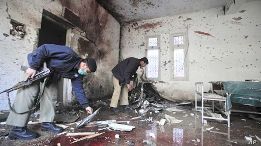 Policemen survey the site of a suicide bomb attack in a police station in Peshawar February 24, 2012.