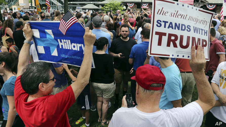 A supporter of Democratic presidential candidate Hillary Clinton and a Republican presidential candidate Donald Trump supporter hold signs as they attend a Memorial Day parade, May 30, 2016, in Chappaqua, N.Y.