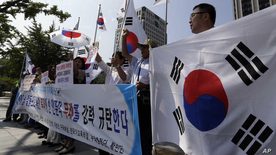 South Korean protesters shout slogans as they hold national flags during a press conference against abrupt cancellation by North Korea of planned reunions for families separated by the Korean War in front of the government complex in Seoul, South Kor