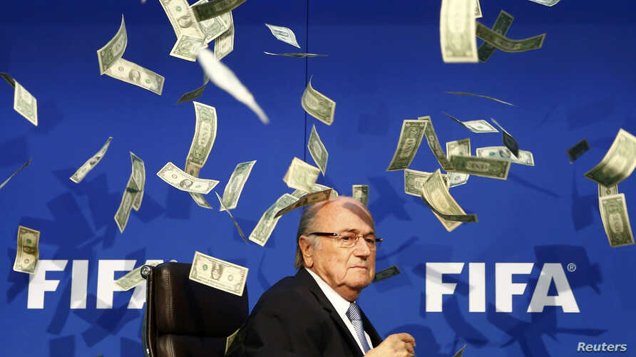 British comedian known as Lee Nelson (unseen) throws banknotes at FIFA President Sepp Blatter as he arrives for a news conference after the Extraordinary FIFA Executive Committee Meeting at the FIFA headquarters in Zurich, Switzerland July 20, 2015.
