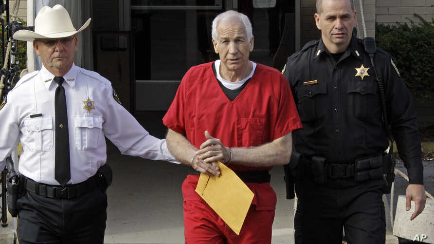 Former Penn State University assistant football coach Jerry Sandusky, center, is escorted by police as he leaves the Centre County Courthouse after being sentenced in Bellefonte, Pa., Tuesday, Oct. 9, 2012.