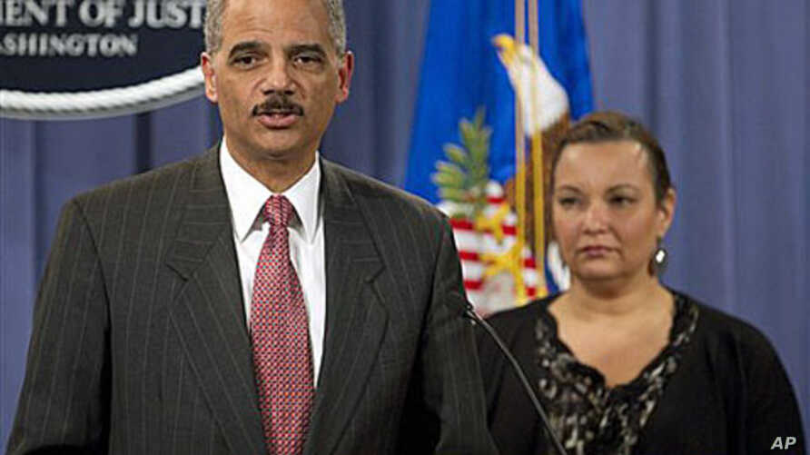 US Attorney General Eric Holder, accompanied by Environmental Protection Agency Administrator Lisa Jackson, gestures during a news conference to announce a civil lawsuit against nine defendants for the Deepwater Horizon oil spill at the Justice Depar