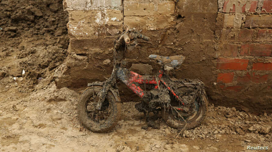 A children's bike leans against a wall covered in mud after rivers breached their banks due to torrential rains, causing flooding and widespread destruction in Carapongo Huachipa, Lima, Peru, March 24, 2017.