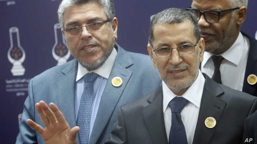 Morocco's new Prime Minister Saadeddine Othmani speaks at the headquarters of the Islamist Justice and Development Party as Moroccan Justice Minister Mustapha Ramid (left) and member of the PJD Mohamed Yatim, look on, in Rabat, Morocco, March 21, 201