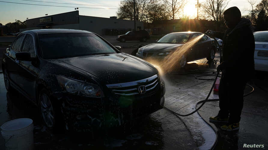 A man washes a car at a small corner carwash in Selma, Ala., Dec. 16, 2017. In Britain hand car washes are often reported for alleged labor abuses and may be regulated in an attempt to stop modern-day slavery.