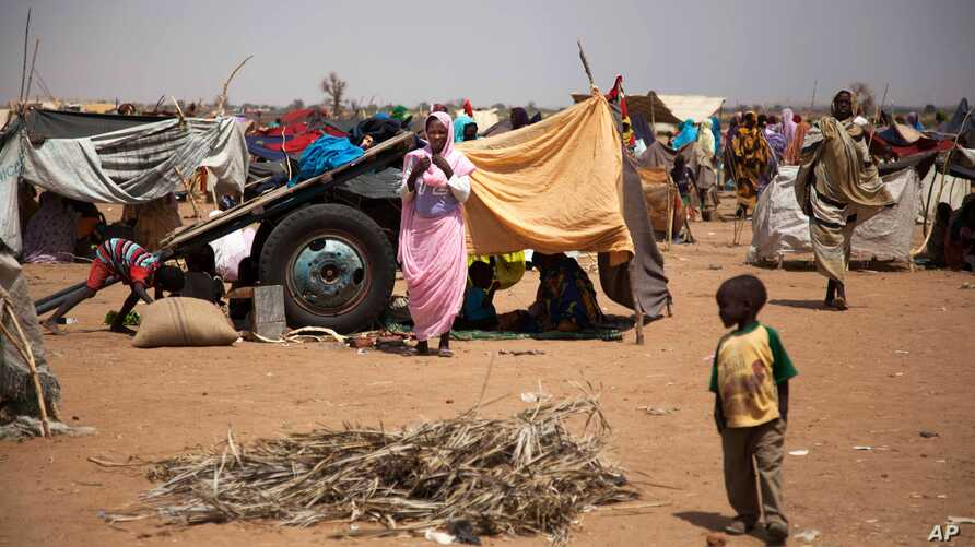 This photo taken March 9, 2014 and released by the United Nations African Union Mission in Darfur (UNAMID) shows a family at the Kalma refugee camp for internally displaced people, south of the Darfur town of Nyala, Sudan.