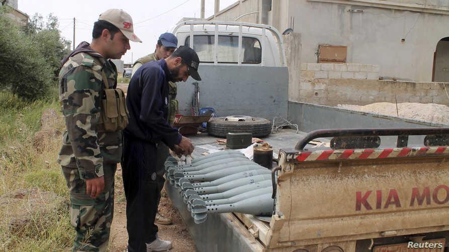 Free Syrian Army fighters stand near mortar shells on a truck in Khirbet Ghazaleh, Daraa, May 3, 2013.