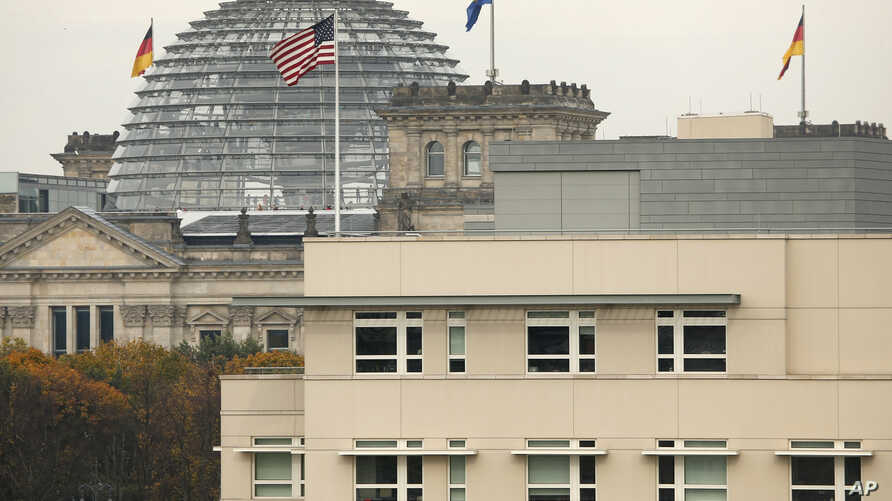 The U.S.  flag flies  on top of the U.S. embassy in front  of the Reichstag building that houses the German  Parliament, Bundestag, in Berlin, Germany, Oct. 25, 2013.