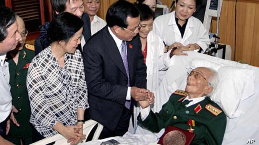 A September 2010 file photo shows Hanoi Communist Party chief Pham Quang Nghi (C-R) shaking hands with Gen. Vo Nguyen Giap in a hospital bed in Hanoi prior to start of celebrations for the city's 1,000th birthday