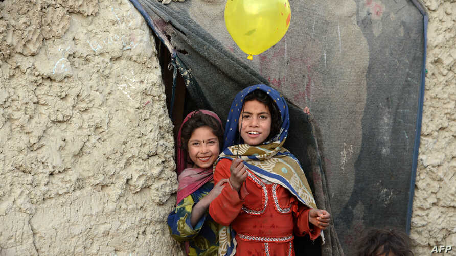 Internally displaced Afghan children play outside their temporary home at a refugee camp in Kabul, Afghanistan.