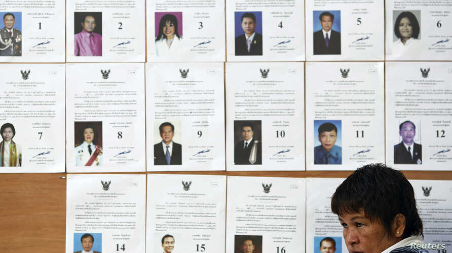 An official sits in front of a board with lists of candidate as she waits for voters at a polling station in Bangkok during a vote to elect a new Senate March 30, 2014. The vote is to elect 77 senators for the 150-seat Senate. The rest are appointed,