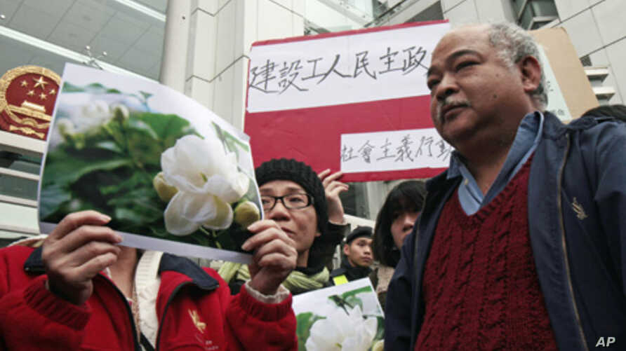 """Protesters hold up pictures of jasmine flowers during a """"Jasmine Revolution"""" protest outside the Chinese liaison office in Hong Kong, February 20, 2011."""