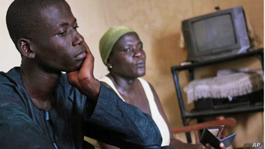 Adama Ouattara, 15, sits with his mother Eugenie Ouattara in the living room of their home, from where father and husband Adimou Ouattara was abducted on December 13 2010, in the Abobo district of Abidjan, Ivory Coast