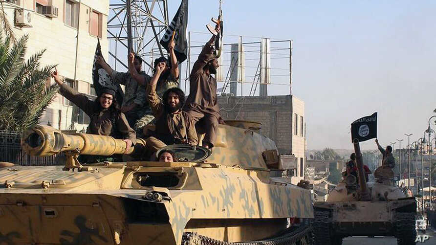 FILE - In this undated file image posted on Monday, June 30, 2014, by the Raqqa Media Center of the Islamic State group, a Syrian opposition group, which has been verified and is consistent with other AP reporting, fighters from the al-Qaida-linked I