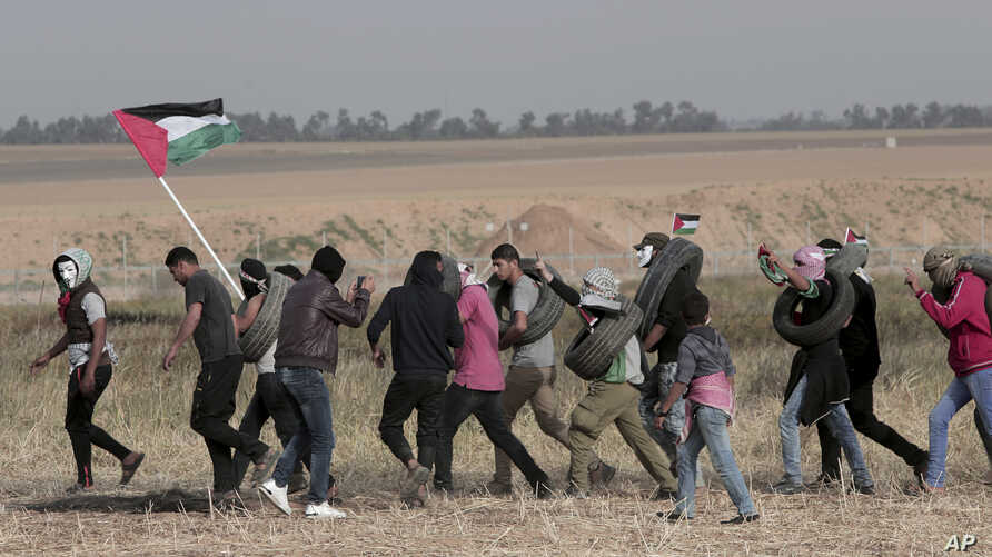 Palestinian masked protesters carrying tires walk toward the border fence during clashes with Israeli troops along Gaza's border with Israel, east of Khan Younis, Gaza Strip,  April 5, 2018.