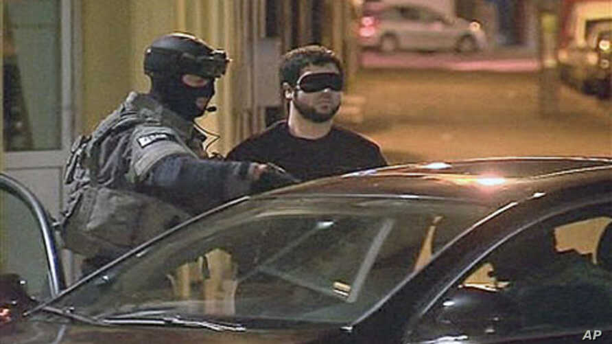 A suspect is led away during an anti-terror sweep in this image taken from TV in Antwerp, Belgium, 23 Nov 2010