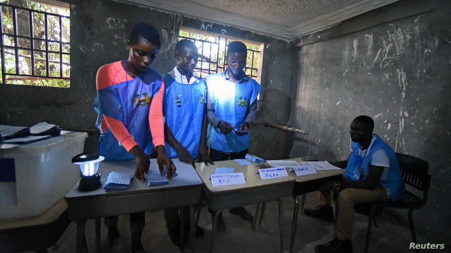 Electoral workers count the votes during a presidential runoff in Freetown, Sierra Leone, March 31, 2018.