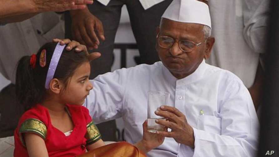 Indian activist Anna Hazare, 73, drinks lime water offered by a child as he breaks his hunger strike in New Delhi, India, April 9, 2011
