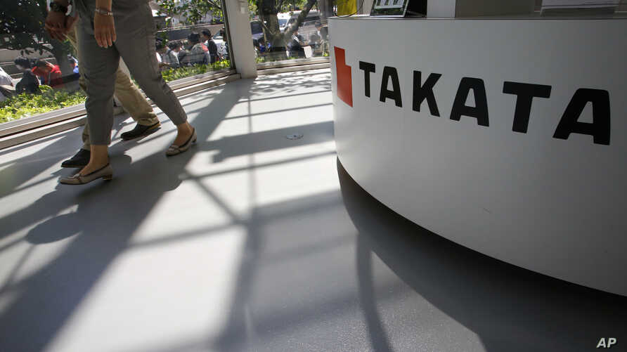 FILE -  Visitors walk by a Takata Corp. desk at an automaker's showroom in Tokyo.