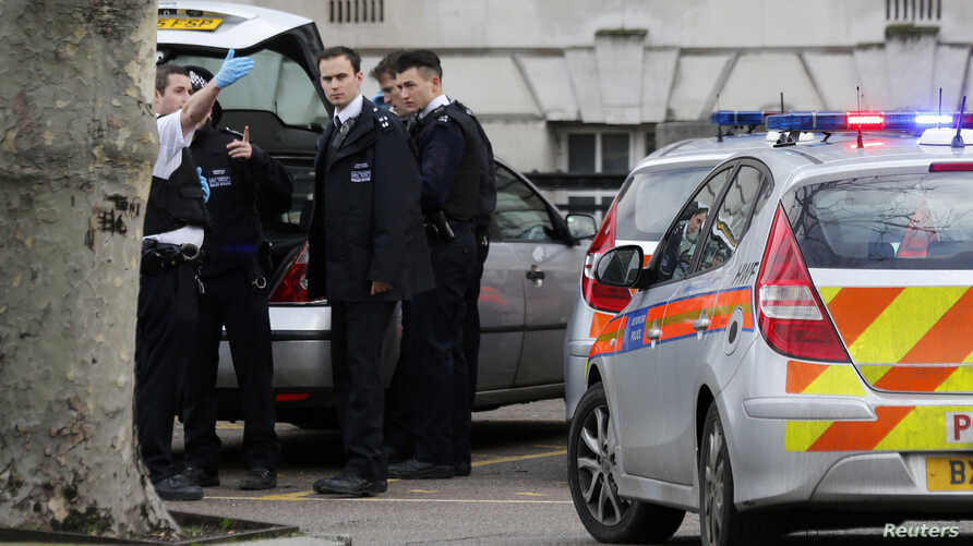 FILE - Police officers attend to the scene of a stabbing in southeast London, Britain, Feb. 1, 2013.