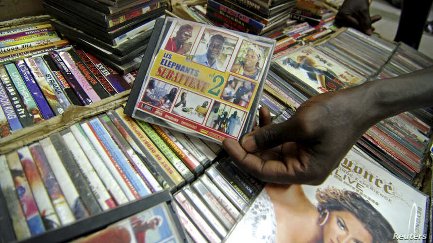 FILE - A shopper holds a pirated copy of a TV sitcom. Movie and TV piracy in Africa is so rampant that some production houses are refusing to distribute in their home countries, preferring to sell their shows only to diaspora Africans in better regul
