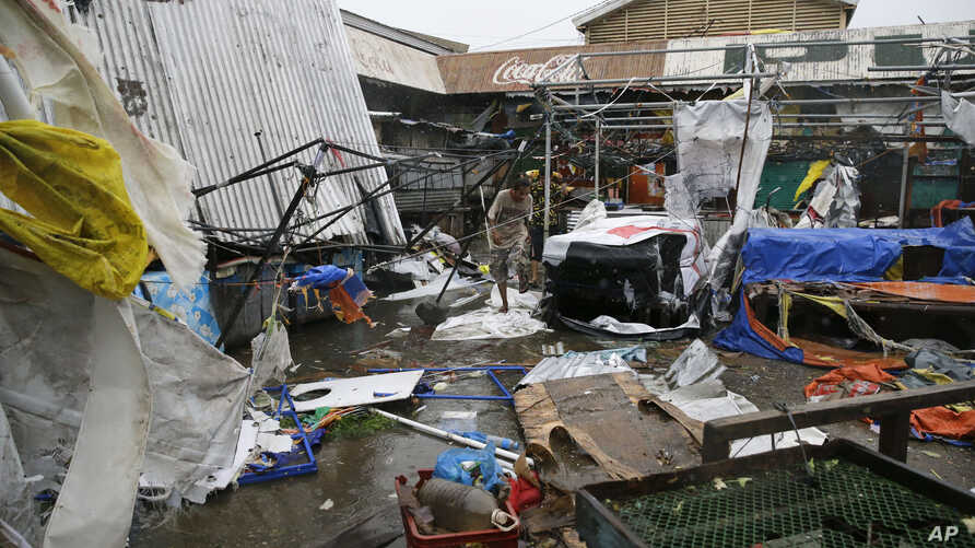 Residents walk along destroyed stalls at a public market from the strong winds of Typhoon Mangkhut in Tuguegrao city in Cagayan province, northeastern Philippines, Sept. 15, 2018.