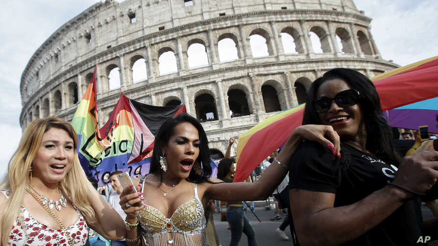 People march past the Colosseum during the a gay-pride parade in Rome, June 11, 2016.