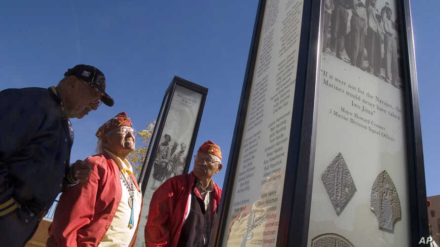FILE - Navajo Code Talkers from left, Albert Smith, Teddy Draper Sr. and Samuel Tso read the names of their brothers-in-arms written on a pillar dedicated to them during the filming of a documentary about them in Gallup, New Mexico, Oct. 28, 2006.
