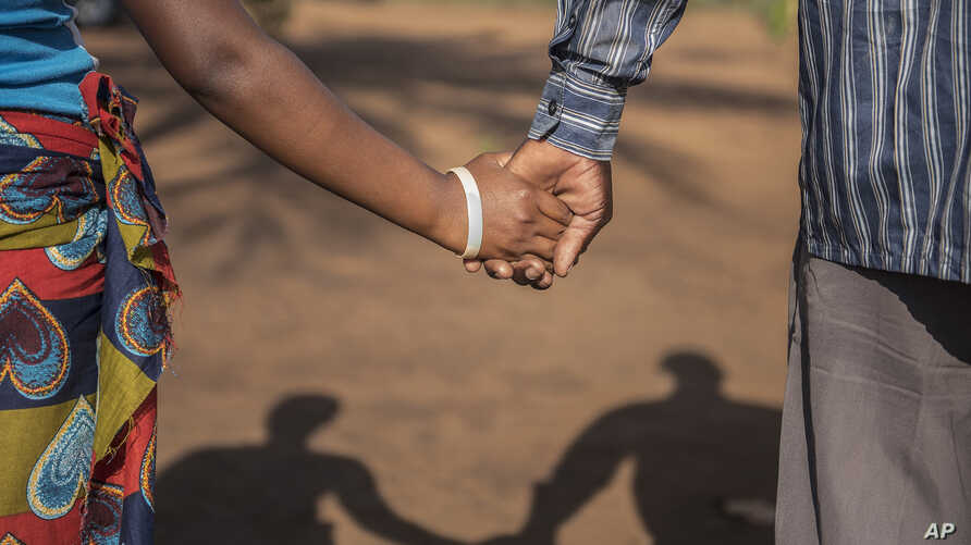A 15-year-old pregnant girl holds hands with her 20-year-old husband-to-be in Guibombo, some 40 kilometers from the city of Inhambane, Mozambique,Nov. 18, 2015.