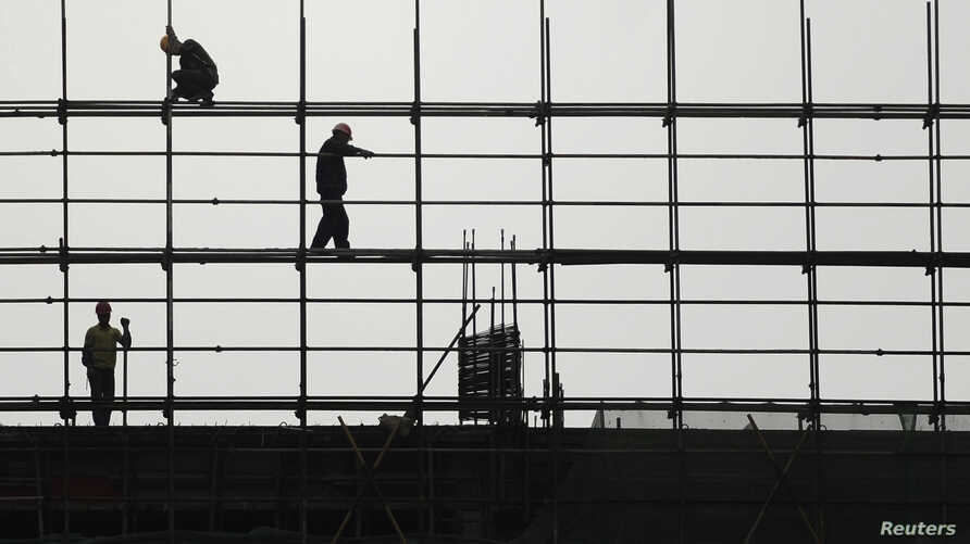 Laborers work on scaffolding at a residential construction site in Hefei, Anhui province, China. Growth is facing downward pressure as exports slow and domestic demand struggles to pick up the slack, partially due to Beijing's campaign to rein in the