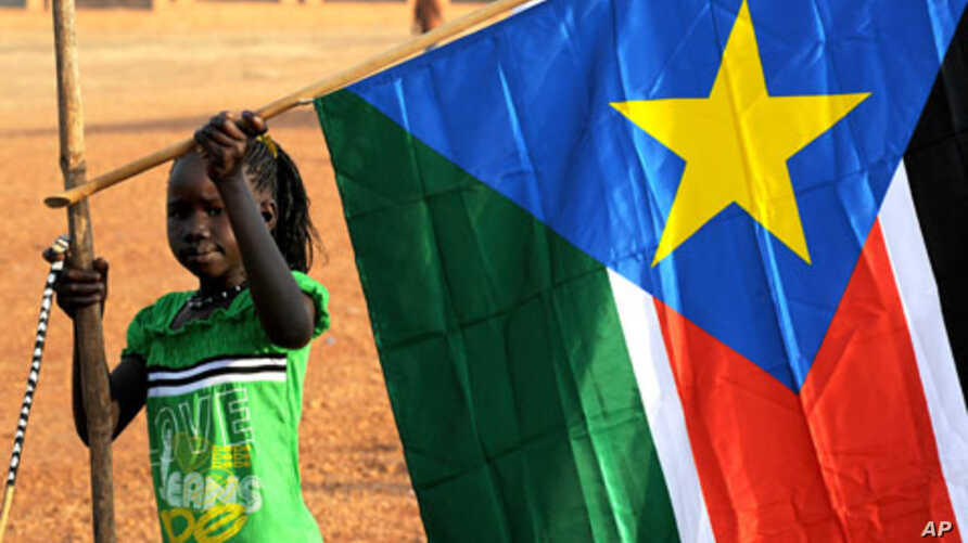 A girl holds a South Sudan flag on January 30 during the announcement of the preliminary results of voting on independence