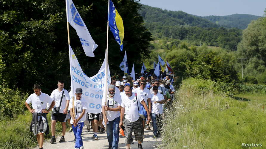 """People walk through a forest near the village of Nezuk Wednesday. Several thousand people started an 85-kilometer (53-mile) """"March for Peace"""" from Nezuk to Srebrenica to retrace the route, in reverse, of Bosnian Muslims fleeing Serb forces in 1995."""