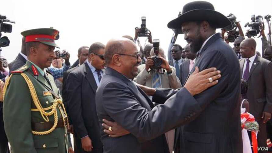 South Sudanese President Salva Kiir (r.) hugs his Sudanese counterpart Omar al Bashir as he arrives at Juba airport on Friday, April 12, 2013. The Sudanese president was visiting South Sudan for the first time since it split from Sudan in 2011.