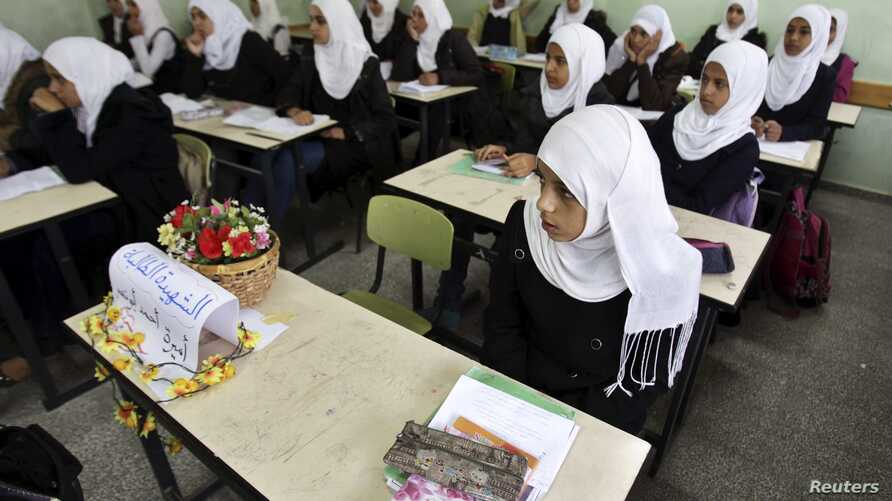 A Palestinian school girl sits next to the chair of her classmate Amera Abu Nasser inside a classroom at al-Awda school in Khan Younis in the southern Gaza Strip November 25, 2012. Abu Nasser was killed with her father after an Israeli air strike on