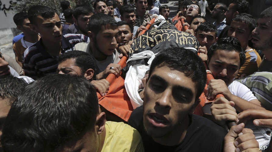 Palestinians carry the body of Islamic Jihad militant  Mohammed Sowelim, who was killed in an Israeli air strike, during his funeral in Jabaliya refugee camp, in the northern Gaza Strip, July 12, 2014.