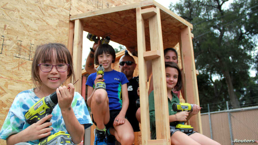 Tiny house builder Elvis Summers (middle) stands inside the shell of a tiny house he is building for a homeless veteran with some of the children helping him build it, in Santa Clarita, California, Aug. 2, 2017.