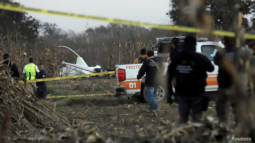 Police and rescue personnel stand at the scene where the helicopter transporting Martha Erika Alonso, governor of the state of Puebla, and his husband Senator Rafel Moreno Valle crashed, in Coronango, Puebla Mexico, Dec. 24, 2018.