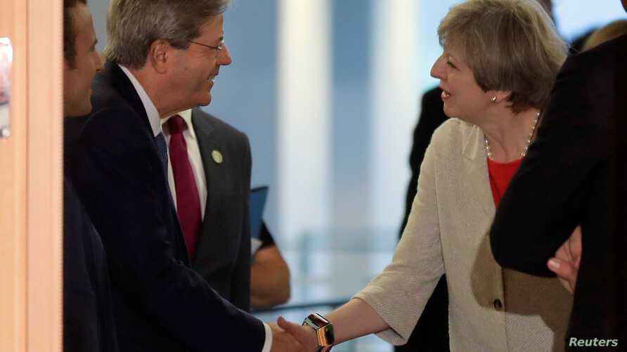 Italian Prime Minister Paolo Gentiloni, welcomes British Prime Minister Theresa May prior to a gathering of European leaders on the upcoming G-20 summit in the chancellery in Berlin, Germany, June 29, 2017.