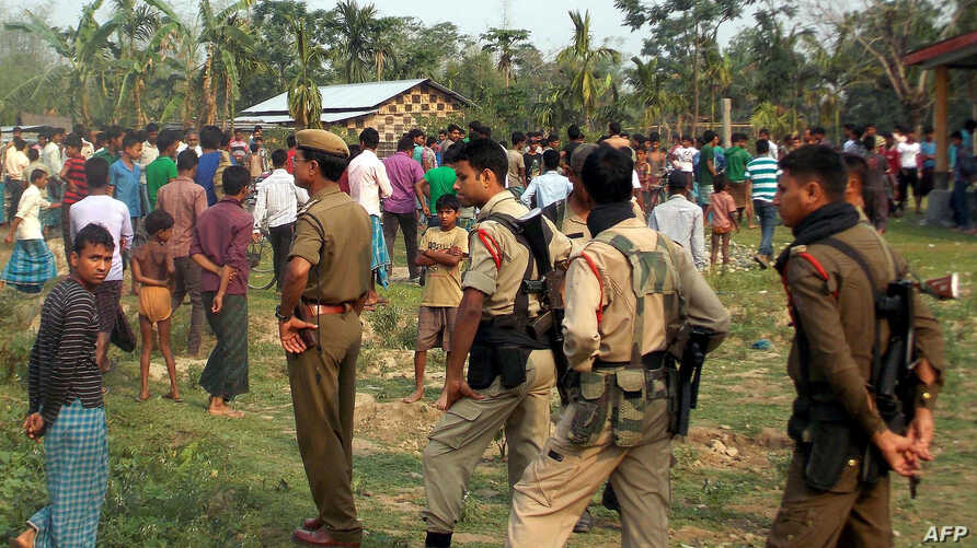 Indian security personnel are pictured as villagers look on following an overnight attack by suspected tribal militants on a village in Kokrajhar, India's northeastern state of Assam, on May 2, 2014.